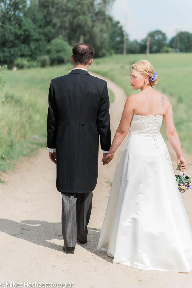 Braut und Bräutigam laufen mit MiKe's